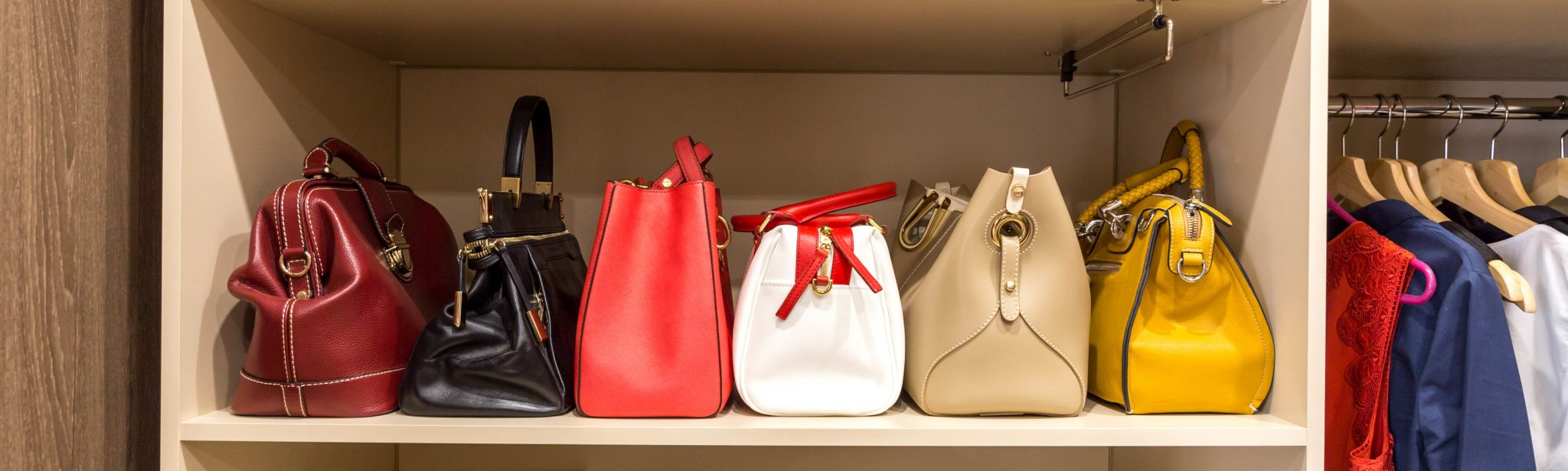 collection of handbags in woman`s wardrobe